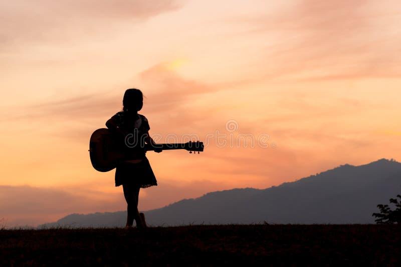 Een silhouet van meisjes die zich met haar gitaar bevinden stock foto's