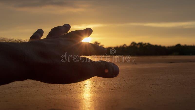 Een silhouet van een menselijke hand die uit bereiken stock afbeeldingen