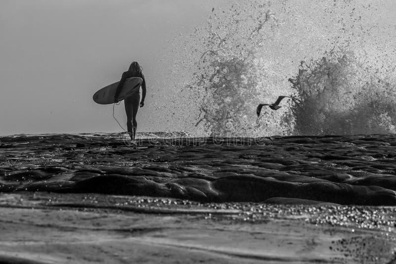 Een silhouet van een surfer die over rotsen als golf lopen verplettert tegen de rots in de afstand stock fotografie