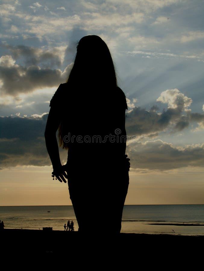 Een silhuette van een slank meisje op het strand stock foto