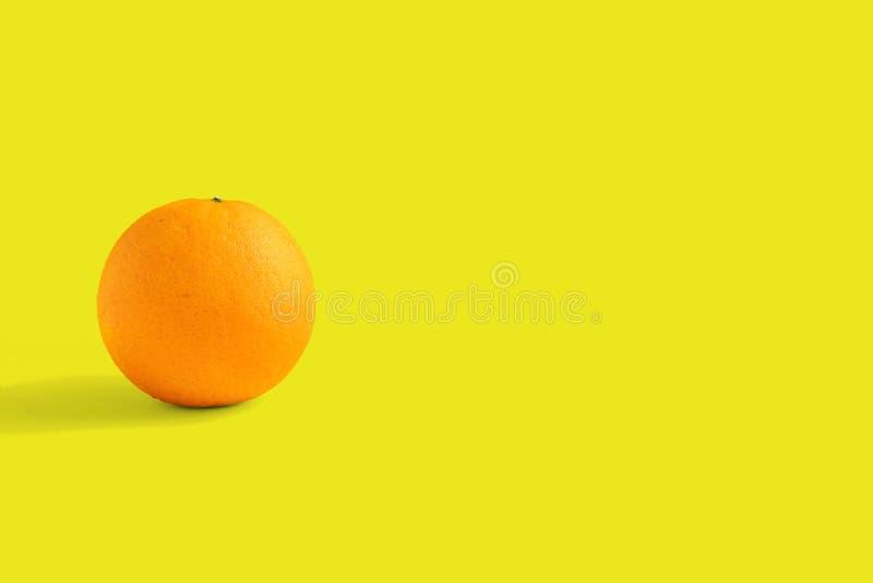 Een sinaasappel op gele achtergrond stock foto's