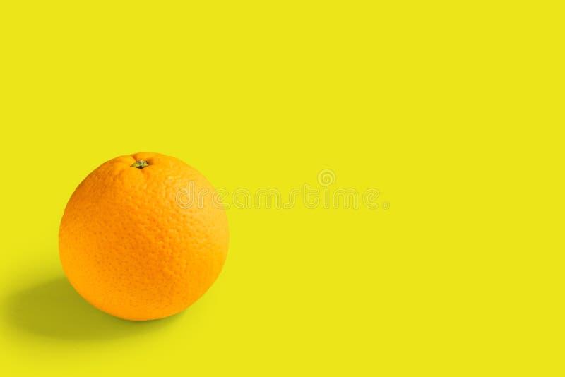 Een sinaasappel op gele achtergrond stock fotografie