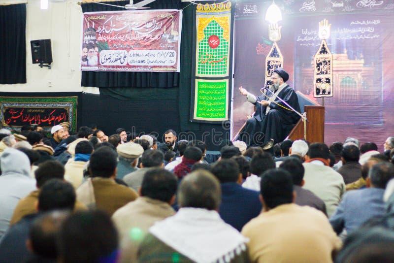 Een sjiïtische geleerde die preek in een Majlis geven terwijl zijn aanhangers hem horen stock afbeelding
