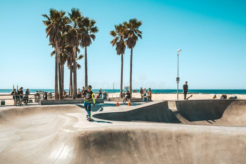 Een skateboarder die met zijn vleet springen stock foto's