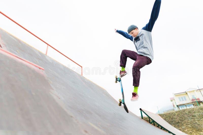 Een skateboardertiener in een hoed doet een truc met een sprong op de helling Een skateboarder vliegt in de lucht royalty-vrije stock foto