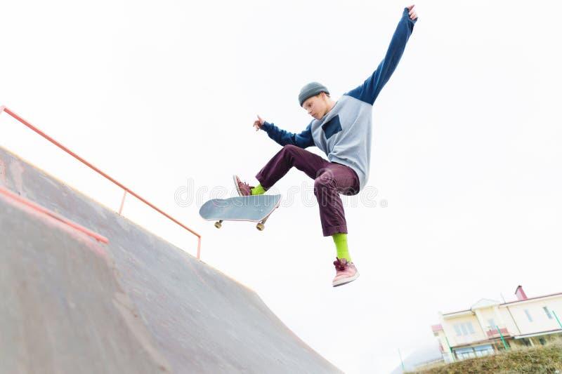 Een skateboardertiener in een hoed doet een truc met een sprong op de helling Een skateboarder vliegt in de lucht royalty-vrije stock foto's