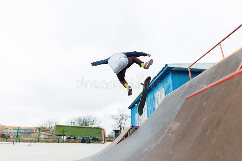 Een skateboardertiener in een hoed doet een truc met een sprong op de helling Een skateboarder vliegt in de lucht royalty-vrije stock fotografie