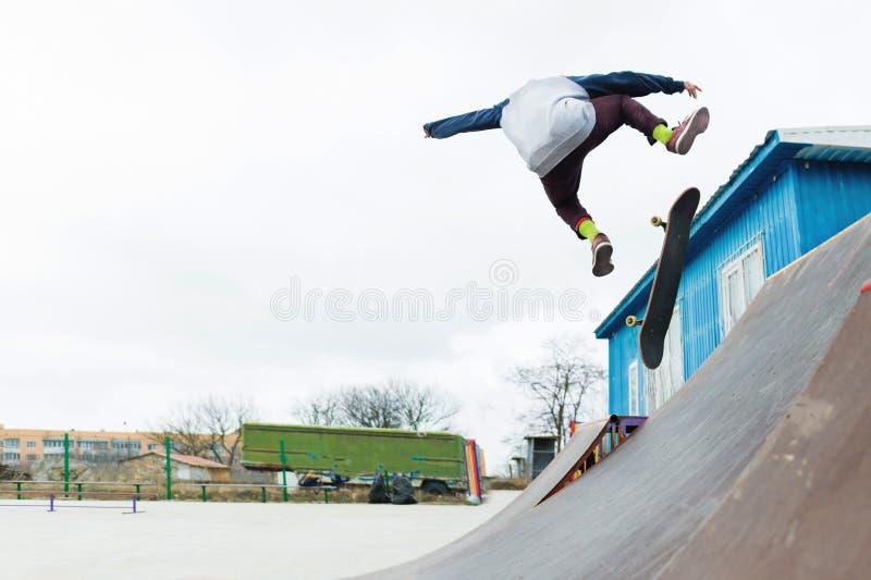 Een skateboardertiener in een hoed doet een truc met een sprong op de helling Een skateboarder vliegt in de lucht royalty-vrije stock afbeelding