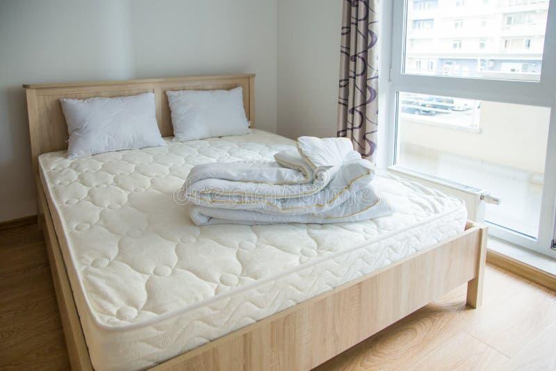 Een slaapkamer in minimalistische stijl met een bed en een garderobe royalty-vrije stock afbeeldingen
