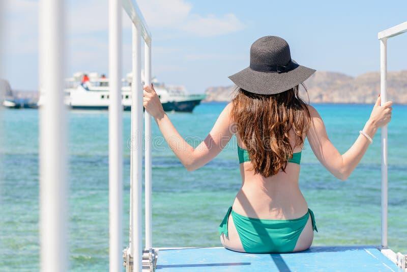 Een slank brunette in een groen zwempak en een hoed op haar hoofd gaat zitten op de overzeese pijler en onderzoekt de afstand Ach stock fotografie