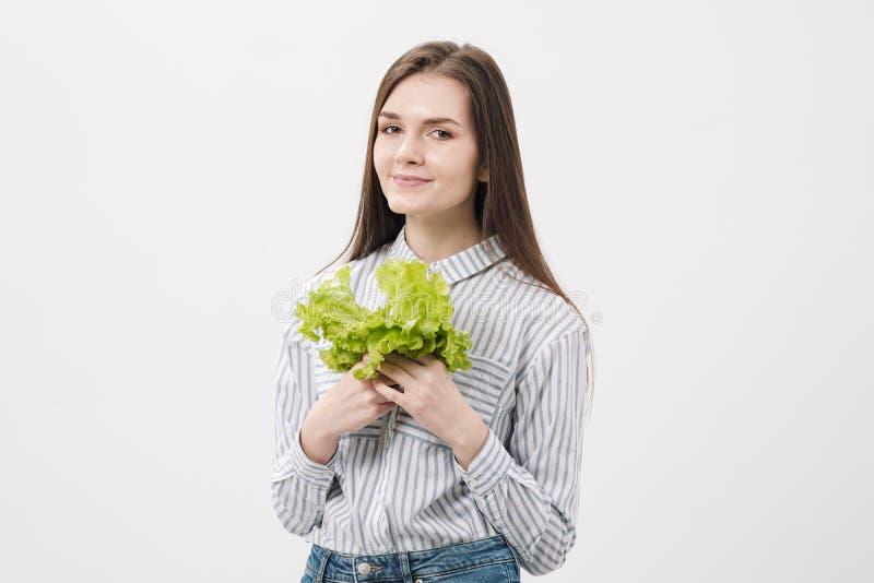 Een slank donkerbruin meisje met lang haar op een witte achtergrond, houdt in haar handen en toont de bladeren van groene vers royalty-vrije stock fotografie
