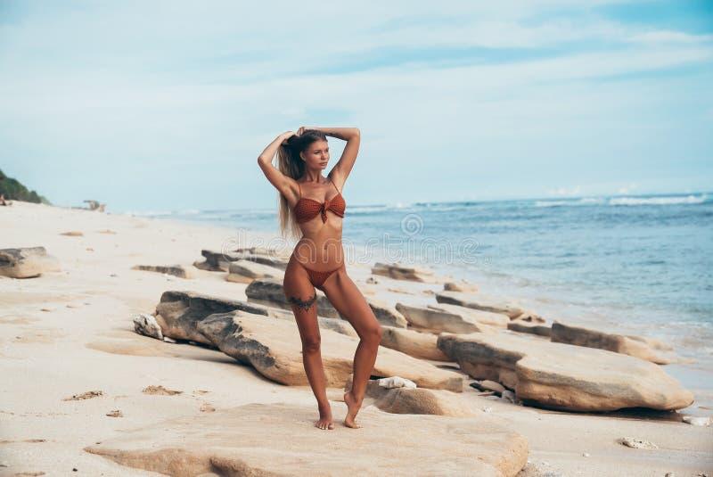 Een slank jong model loopt langs een verlaten strand alleen en bewondert de golven van de blauwe oceaan Het meisje is binnen gekl stock afbeeldingen