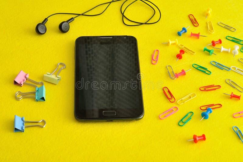 Een slanke die telefoon met oortelefoons met het vouwen van klemmen worden getoond stock fotografie