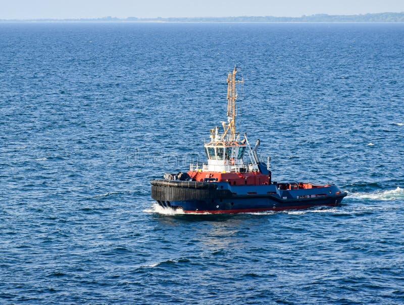 Een sleepboot navigeert op het overzees, op de achtergrond kan de kust worden gezien royalty-vrije stock afbeelding