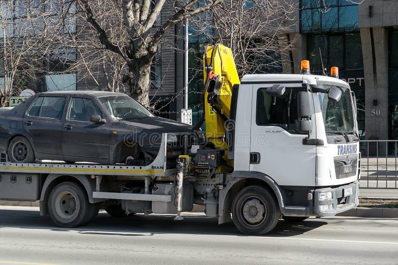 Een slepenvrachtwagen met haak en de ketting vervoerden een auto in de loop van de dag zonder een voorwiel langs de stadsstraat stock foto