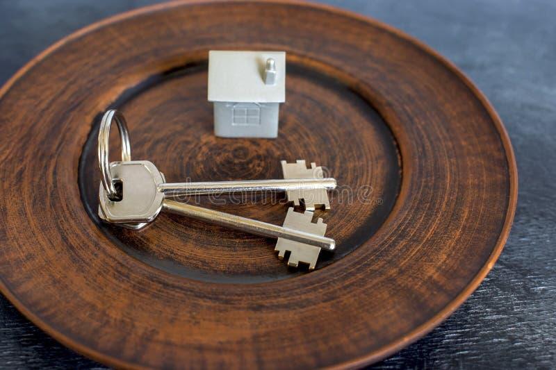 Een sleutelbos ligt op een uitstekende plaat, samen met een imitatie van het huis in de vorm van een metaallay-out stock afbeeldingen