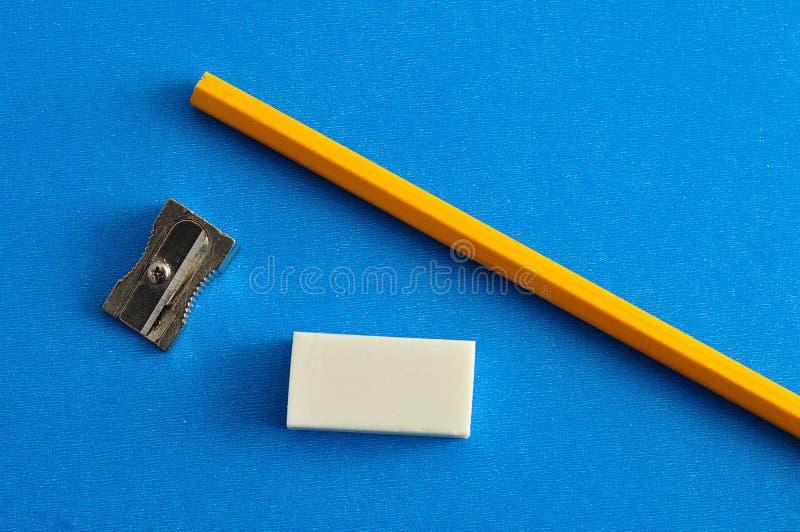 Een slijper, een gom en een geel potlood stock foto