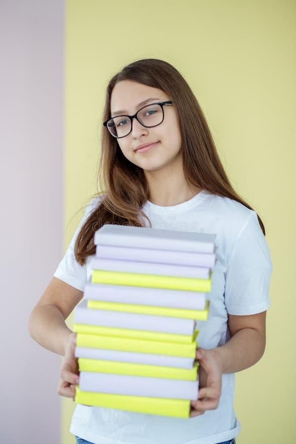 Een slim tienermeisje houdt vele verschillende handboeken Een kind met glazen Concept onderwijs, hobby, studie en de dag van het  royalty-vrije stock afbeelding