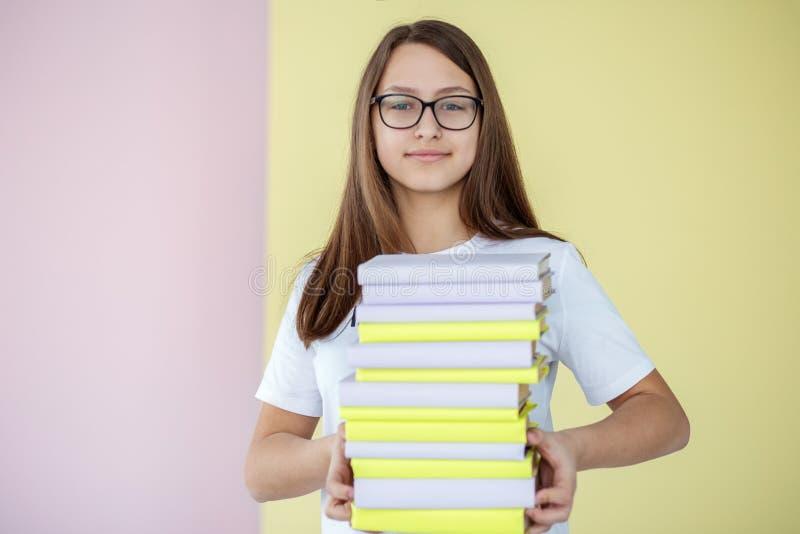 Een slim tienermeisje houdt vele verschillende handboeken Terug naar School Concept onderwijs, hobby, studie en de dag van het we stock afbeeldingen