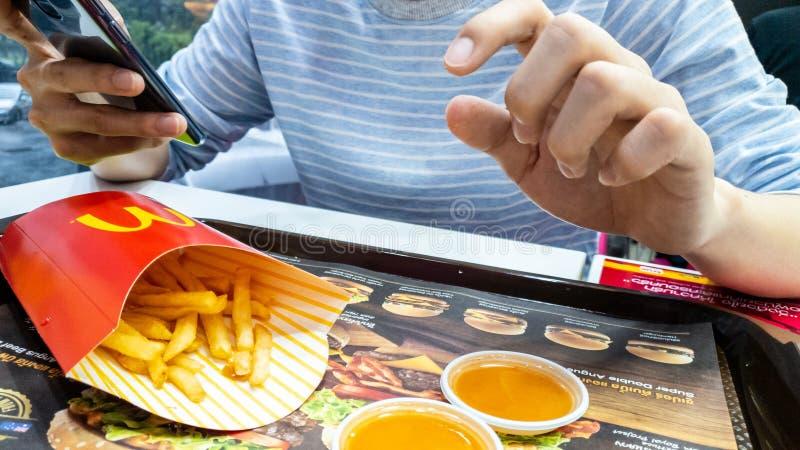 een slimme telefoon van het mensengebruik en het eten van frietencontainer in rode pakket en Spaanse pepersaus bij de reclame van royalty-vrije stock foto