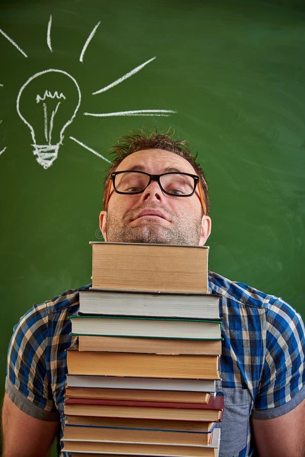 Een slordige ongeschoren jonge mens in glazen houdt een zware stapel boeken stock foto