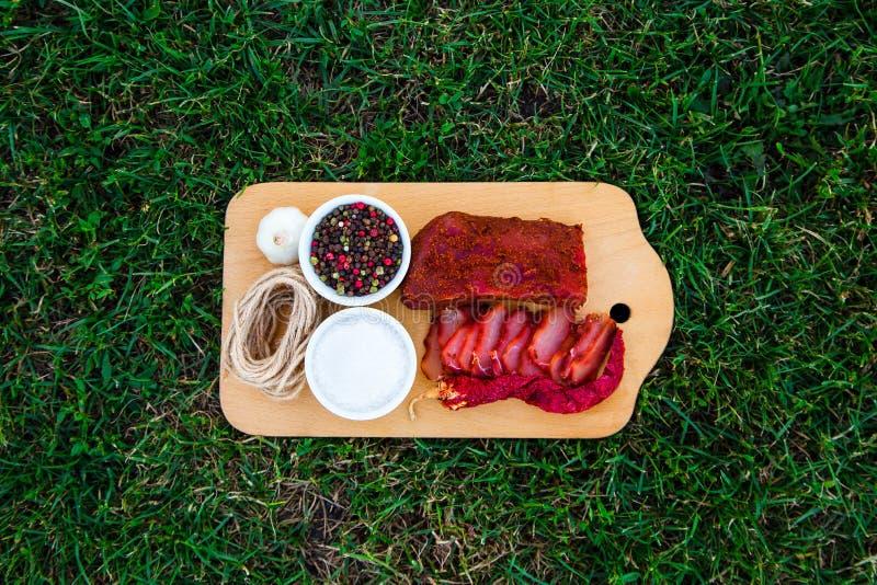 Een smakelijk stuk van vlees met kruiden wordt voorgesteld op houten stock afbeeldingen