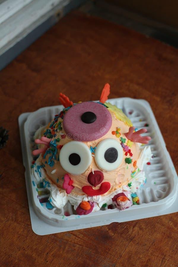Een smakelijke cake met een grappig die gezicht met details door de alleen jonge geitjes wordt gemaakt en wordt verfraaid royalty-vrije stock afbeeldingen