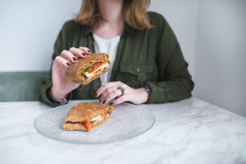 Een smakelijke sandwich in de handen van een jong meisje Sandwich in close-up en in nadruk royalty-vrije stock foto