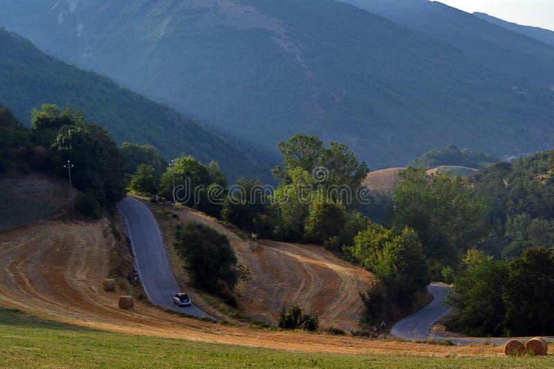 Een smalle weg die in de bergen tussen de gebieden beklimmen stock foto's