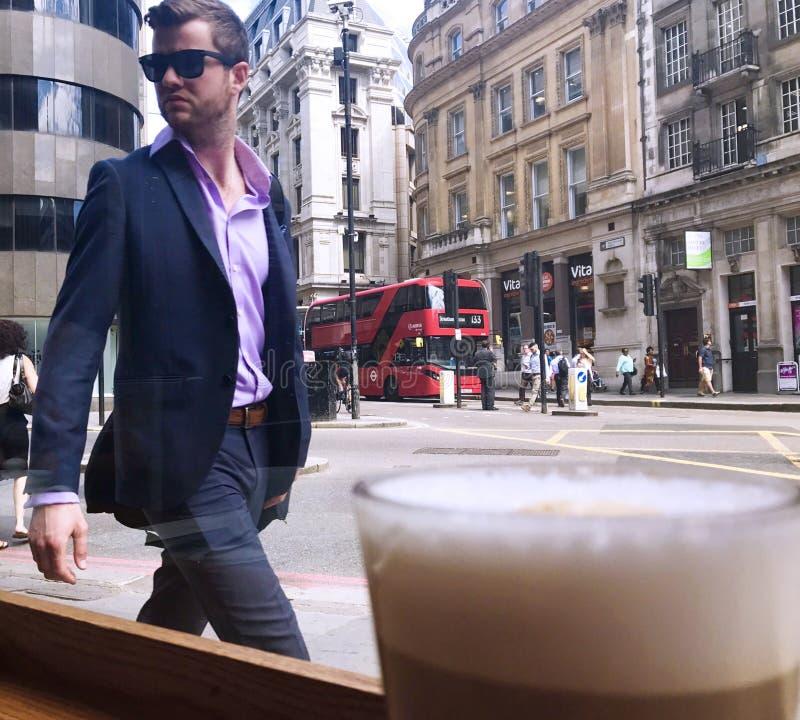 Een smartly geklede jonge mens bekijkt zijn eigen gedachtengang in een venster van de koffiewinkel in de Stad van Londen, het UK  stock fotografie