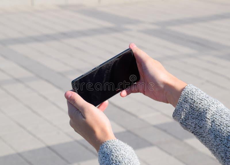 Een smartphone is in de handen van een vrouw Mededeling die een smartphone gebruiken royalty-vrije stock foto's