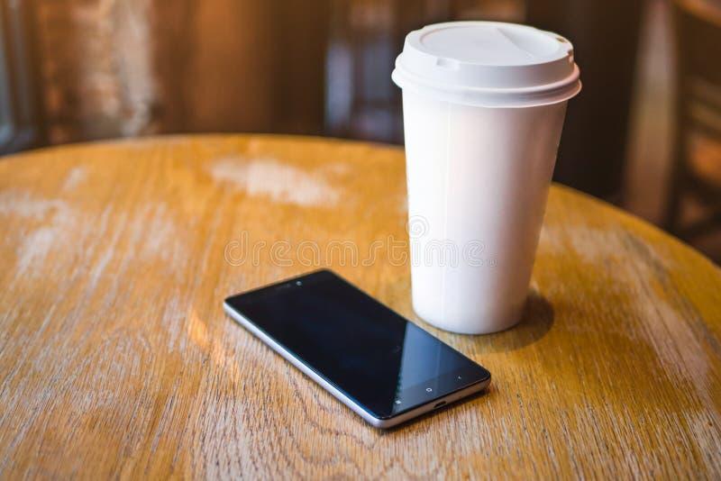 Een smartphone rust op een lijst in een koffie, stock afbeelding