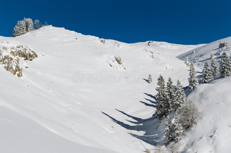 Een sneeuwhelling bij de bovenkant van een bergketting met een duidelijke blauwe hemel op een zonnige dag royalty-vrije stock foto's