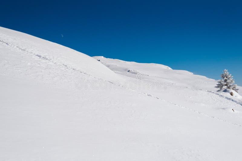 Een sneeuwhelling bovenop de berg met een duidelijke blauwe hemel op een zonnige dag royalty-vrije stock fotografie
