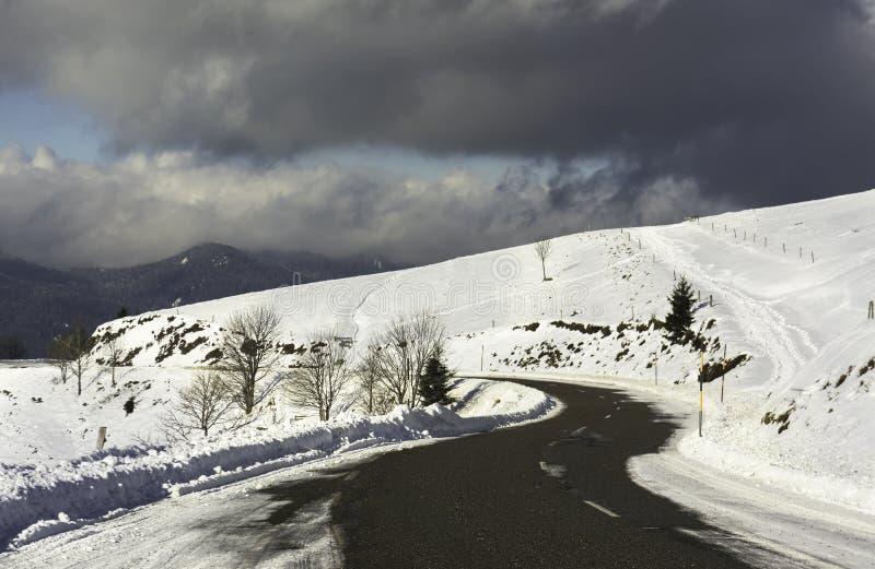 Een sneeuwwegkromme in de bergen met een bewolkte hemel - horizont stock foto's