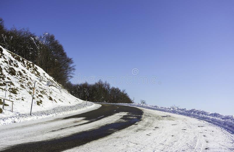 Een sneeuwwegkromme in de bergen met een groot gediplomeerd blauw royalty-vrije stock foto's