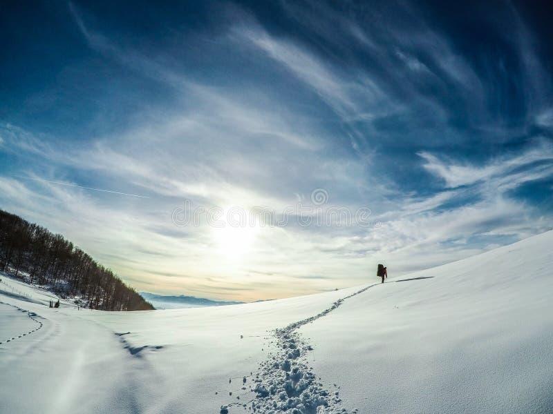 Een snowboarde die tot zijn manier maken omhoog een berg om een rit te maken stock foto's