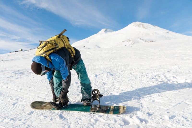 Een snowboarder met een rugzak op zijn rug maakt snowboard banden vast stock fotografie