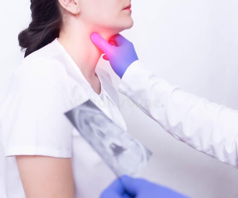 Een specialist arts diagnostiseert een meisjess keelpijn door voor de aanwezigheid van ontsteking te palperen en te zwellen, keel royalty-vrije stock afbeelding