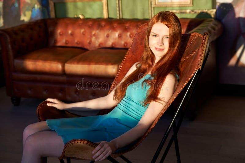 Een spectaculair roodharig meisje zit in een leerleunstoel tegen de achtergrond van zonlicht en modieuze binnenlands royalty-vrije stock foto