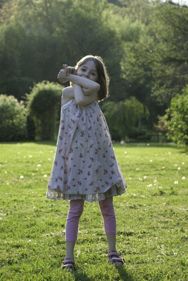 Een speels en gelukkig jong meisje in een zonnige tuin stock afbeeldingen