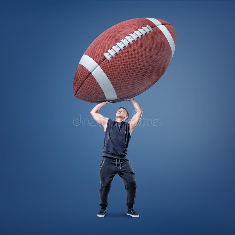 Een spier atletische mens heeft probleem om een reuze Amerikaanse voetbalbal over zich te houden stock afbeelding
