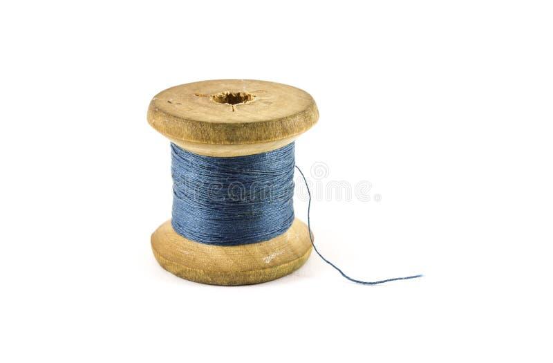 Een spoel met blauwe draden stock afbeelding