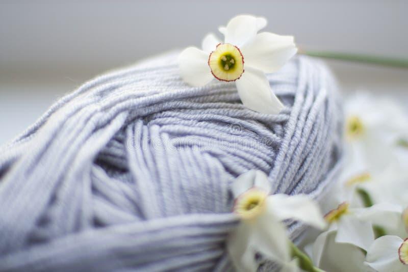 Een spoel van grijs garen in bloemen royalty-vrije stock afbeeldingen