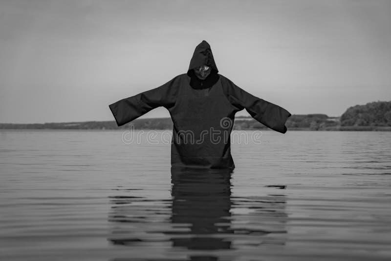 Een spook in een zwarte mantel bevindt zich in het meer dat met handen op de achtergrond van aard worden opgeheven Het spoor word stock foto