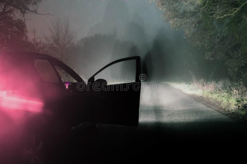 Een spookachtig cijfer naast een auto op een griezelige mistige weg bij bocht stock foto