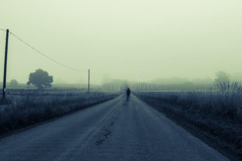 Een spookachtige vage mens die zich in het midden van de weg op een angstaanjagende nevelige ochtend bevinden Met een donkere, hu royalty-vrije stock fotografie