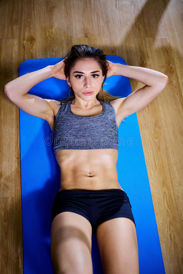Een sportenmeisje doet abs op vloer in de gymnastiek Mening van hierboven royalty-vrije stock foto