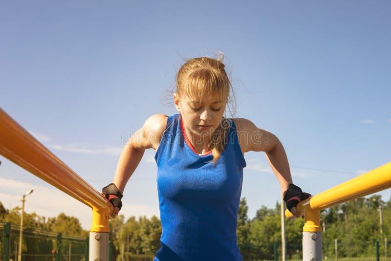 Een sportenmeisje leidt in het park op de rekstokken op royalty-vrije stock afbeeldingen