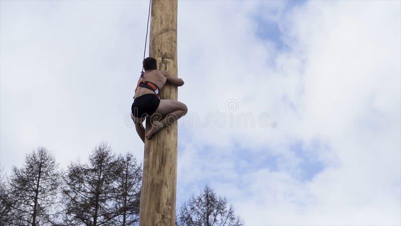 Een sportieve mens die een houten pool beklimmen om de doos met de prijs, Slavische vakantie Maslenitsa Shrovetide te krijgen act stock fotografie